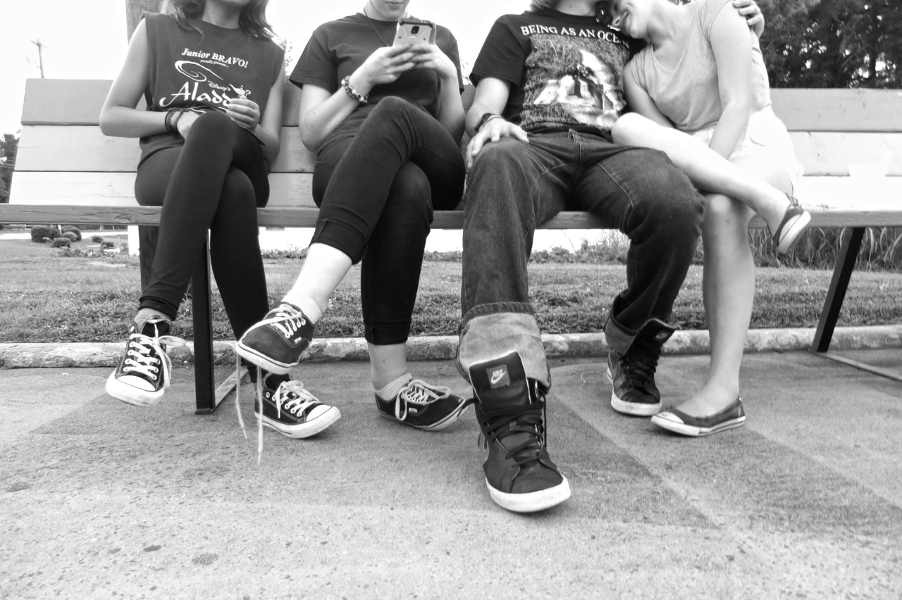 black and white photo of teenagers feet