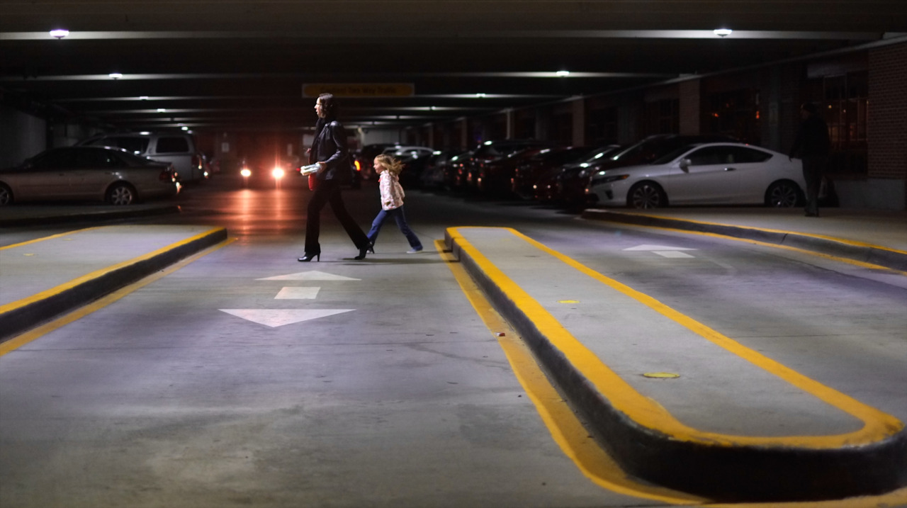 photo of a mom and child walking in a parking garage