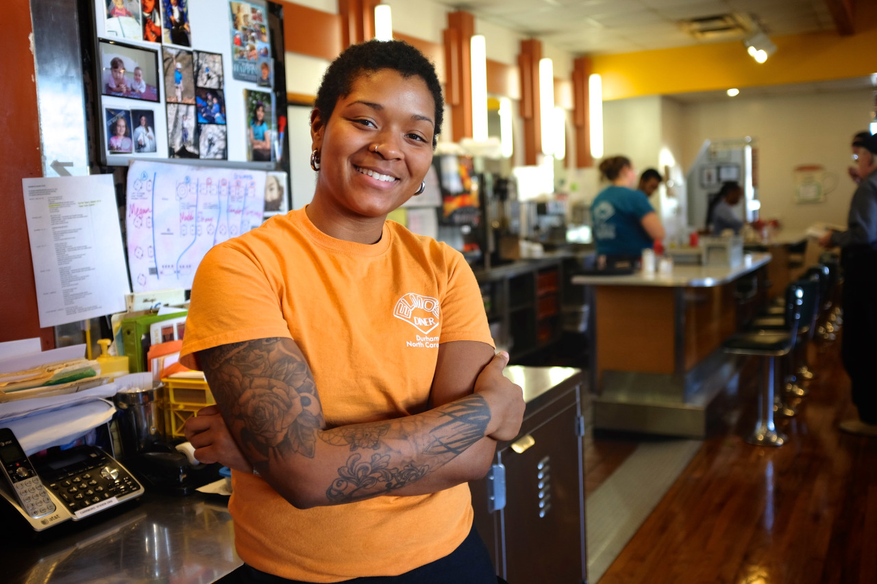 young african-american waitress with tattoos smiling