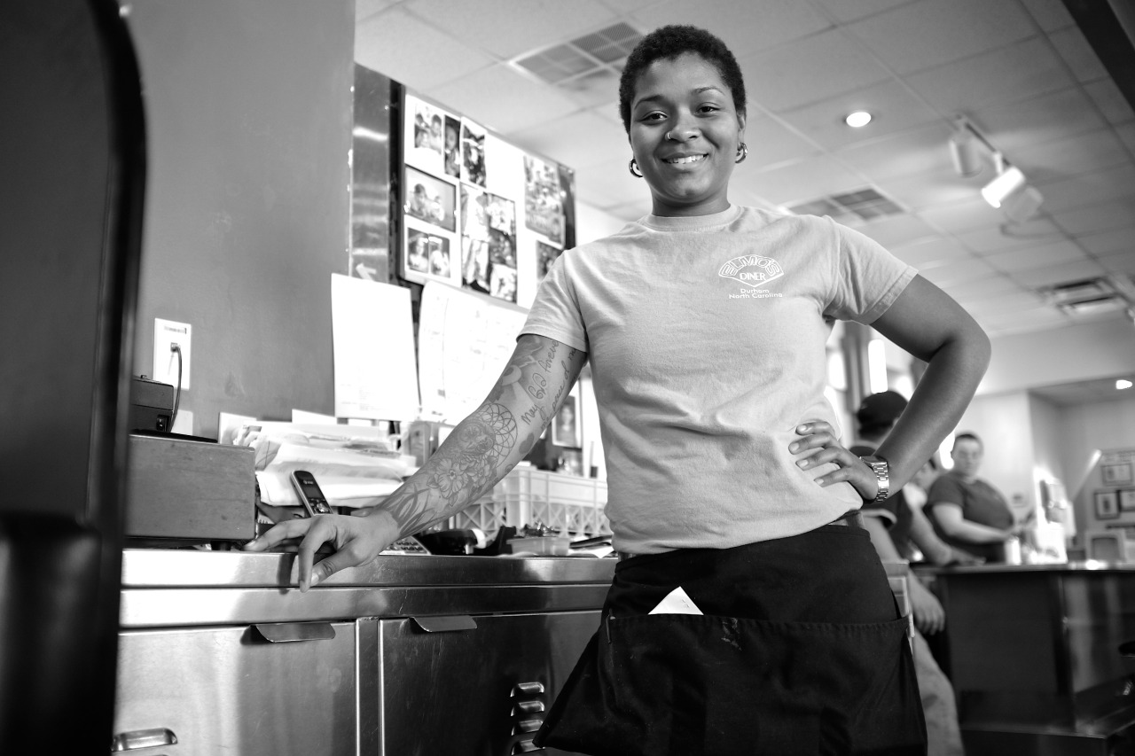 Black and White photo of a young african-american waitress at a restaurant