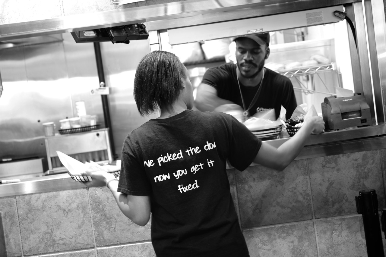 girl at hot dog shot with a slogan on the back 'we picked the dog, now you get it fixed.'