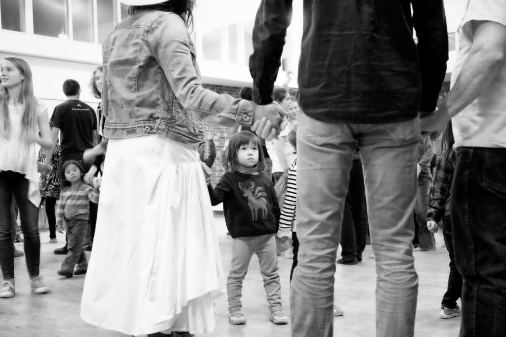 black and white photo at a country dance showing a little girl at the level of adult's legs
