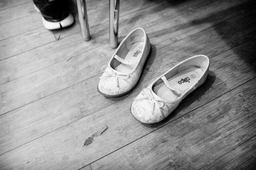 photo of a little girl's dance slippers on a wooden floor