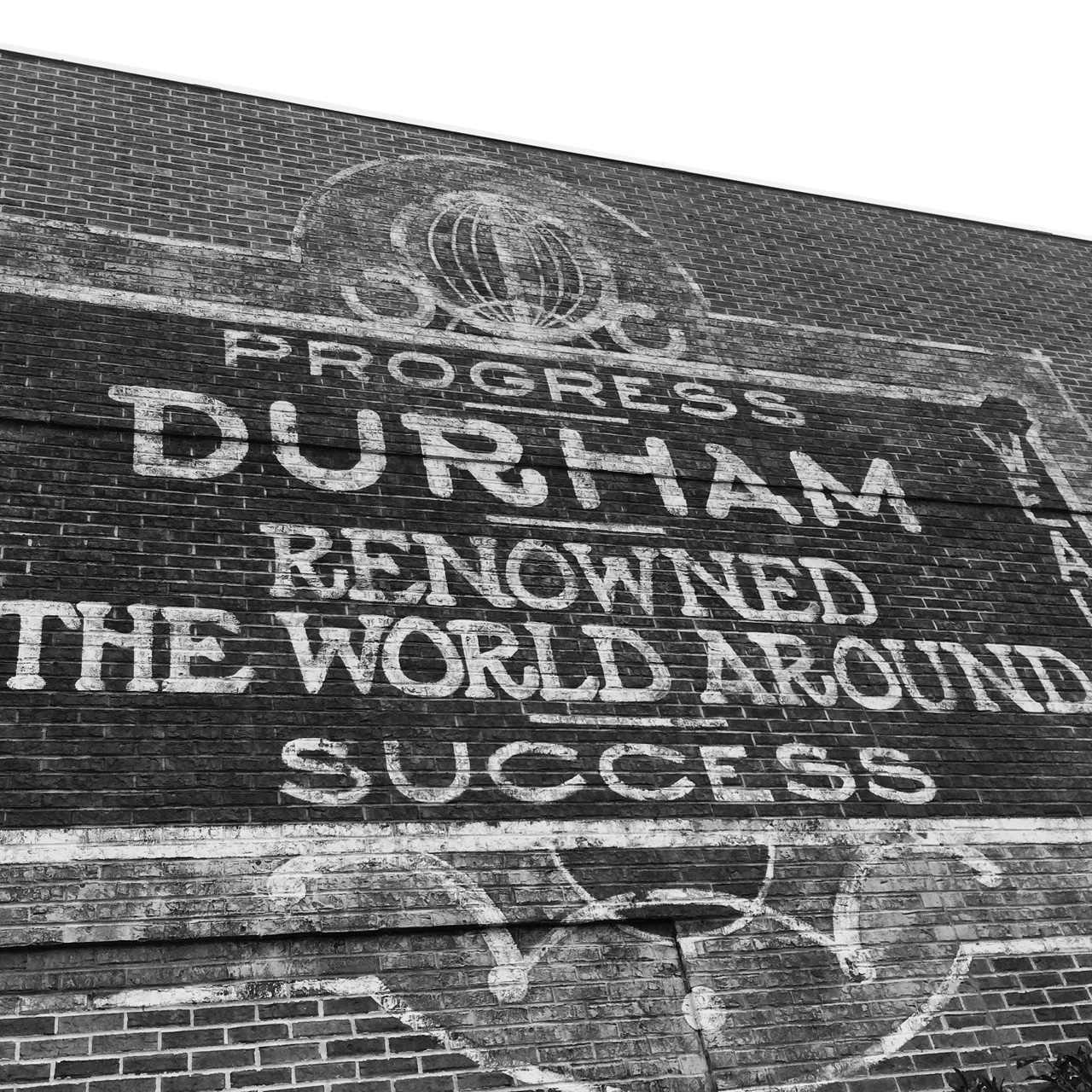 Reproduction of a historic Durham NC sign saying: Progress. Durham Renowned the world around. Success.