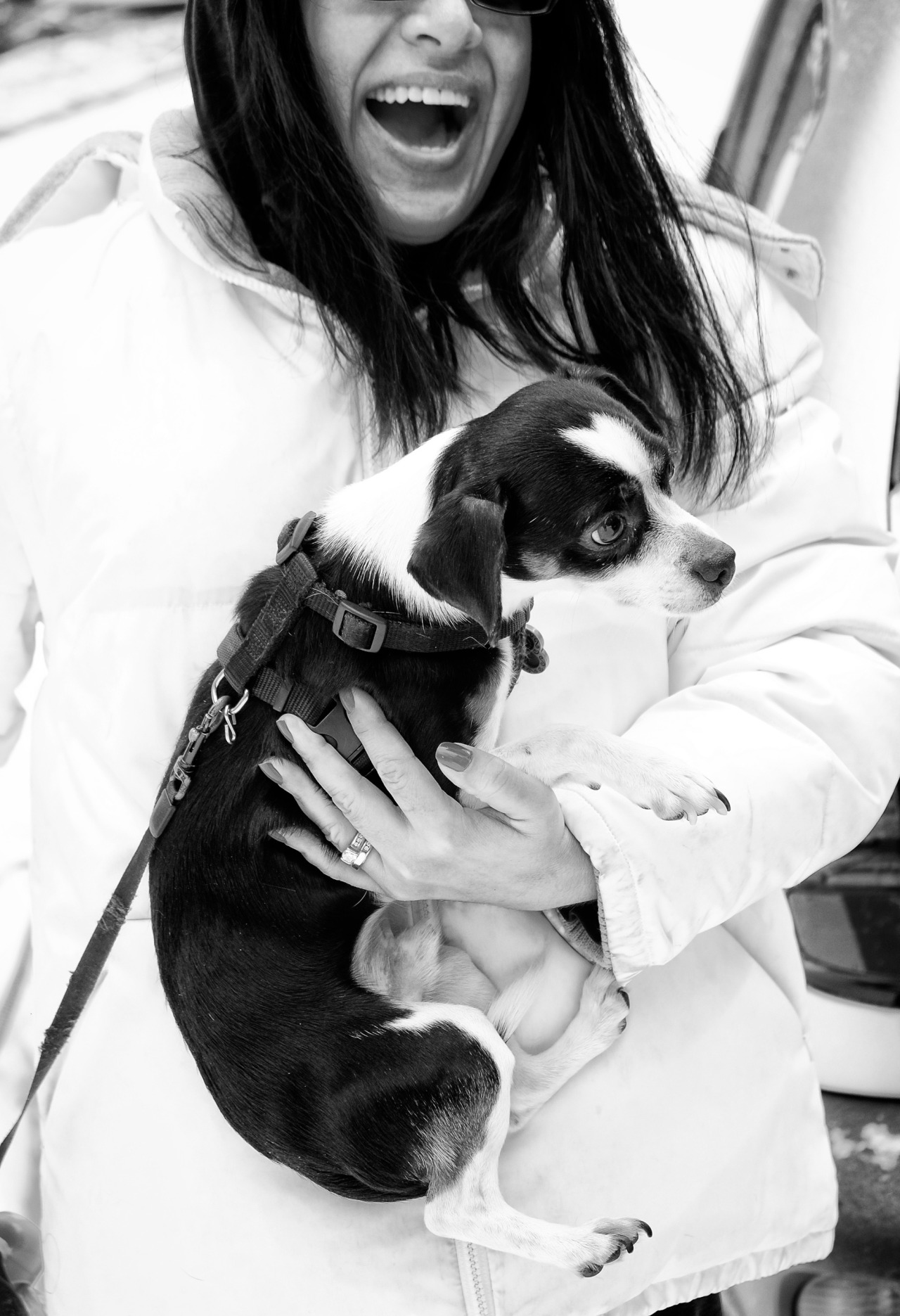 black and white photo of woman in white coat holding a black and white dog
