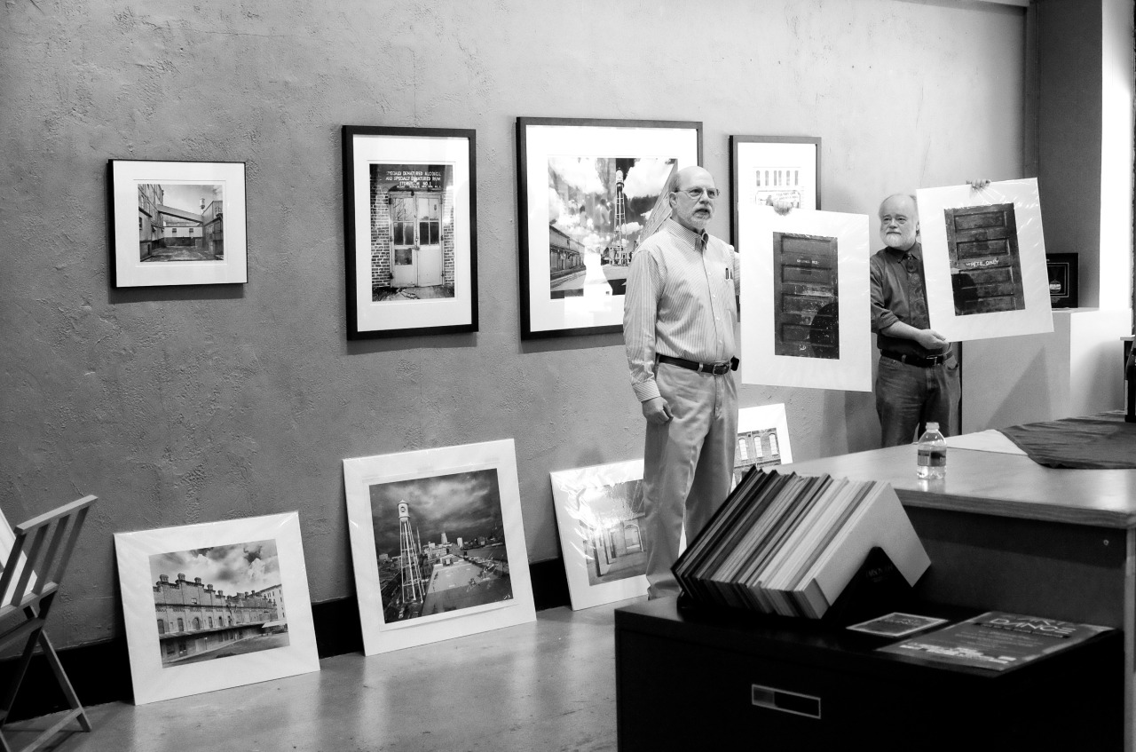 monochrome image of a man at a photo art gallery giving a talk