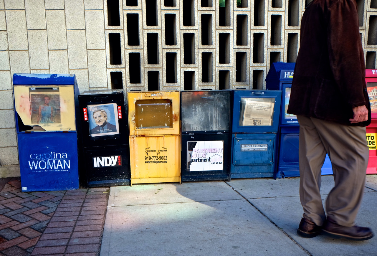 Photo of beat up looking magazine distribution boxes with the legs of a man walking by