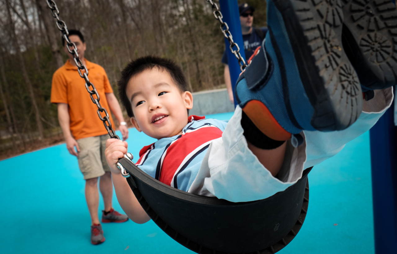 photo of a young asian boy smiling on a swing