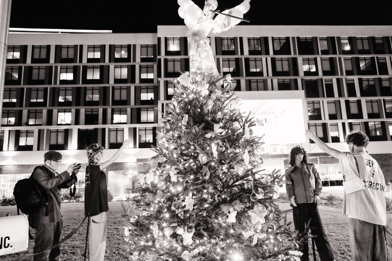 a black and white image of a young photographer looking similar to the mannequins dummies standing by a Christmas tree