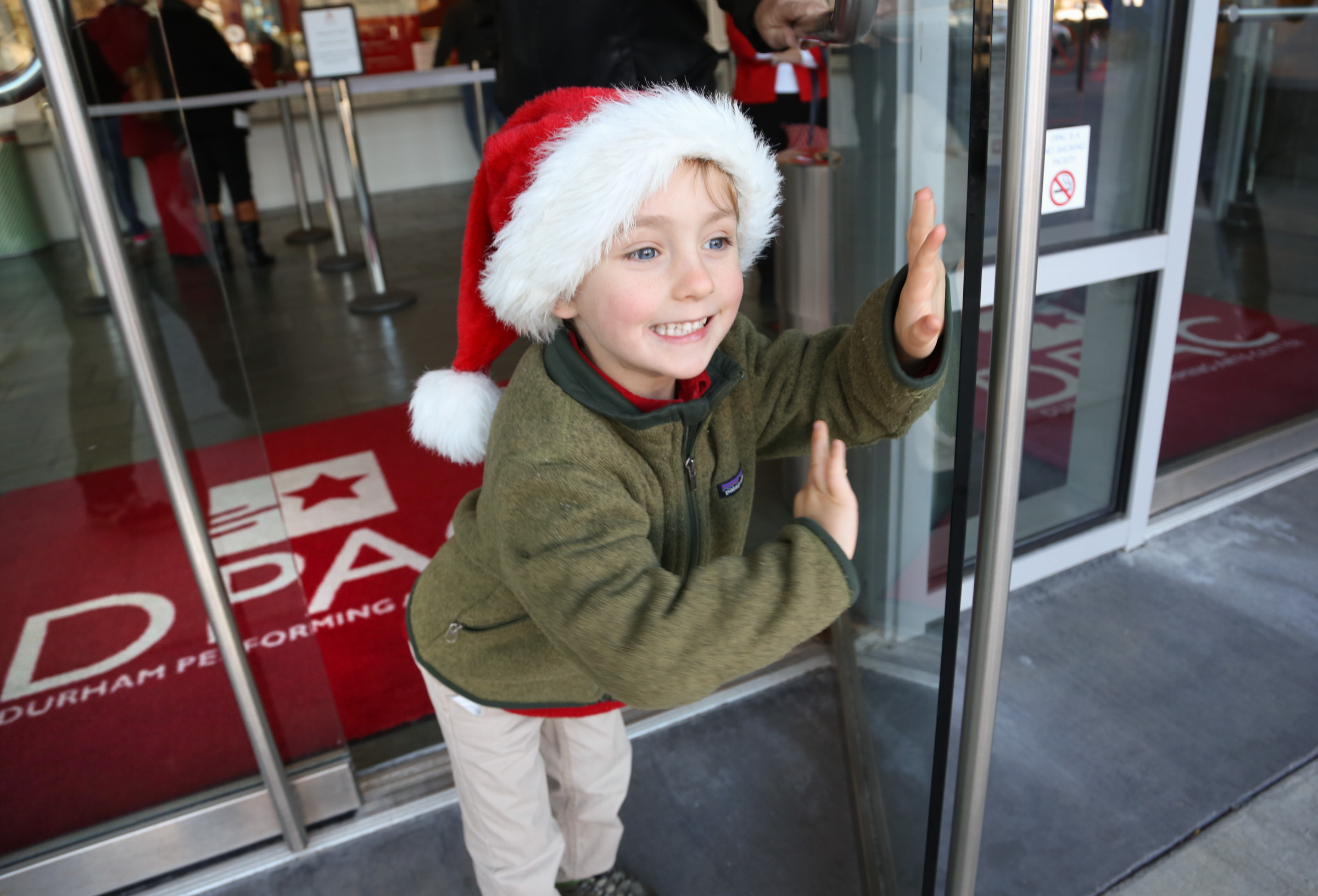 photo of boy in santa cap opening door to DPAC