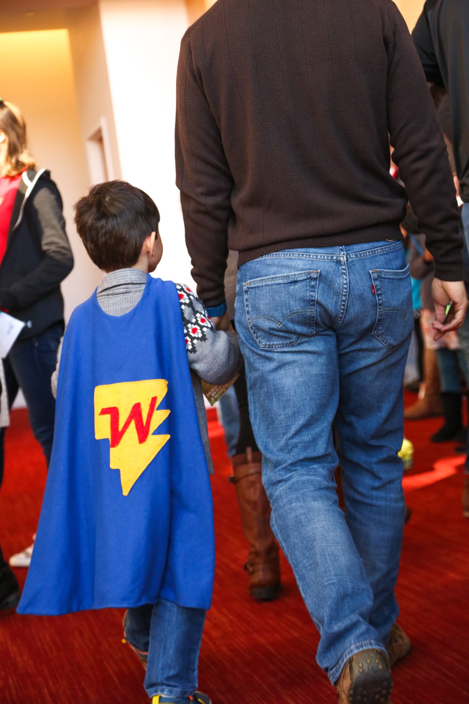 photo from behind of boy in blue superhero cape