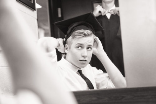 Image of a high school grad boy adjusting his cap in the mirror while another boy adjusts his bow tie