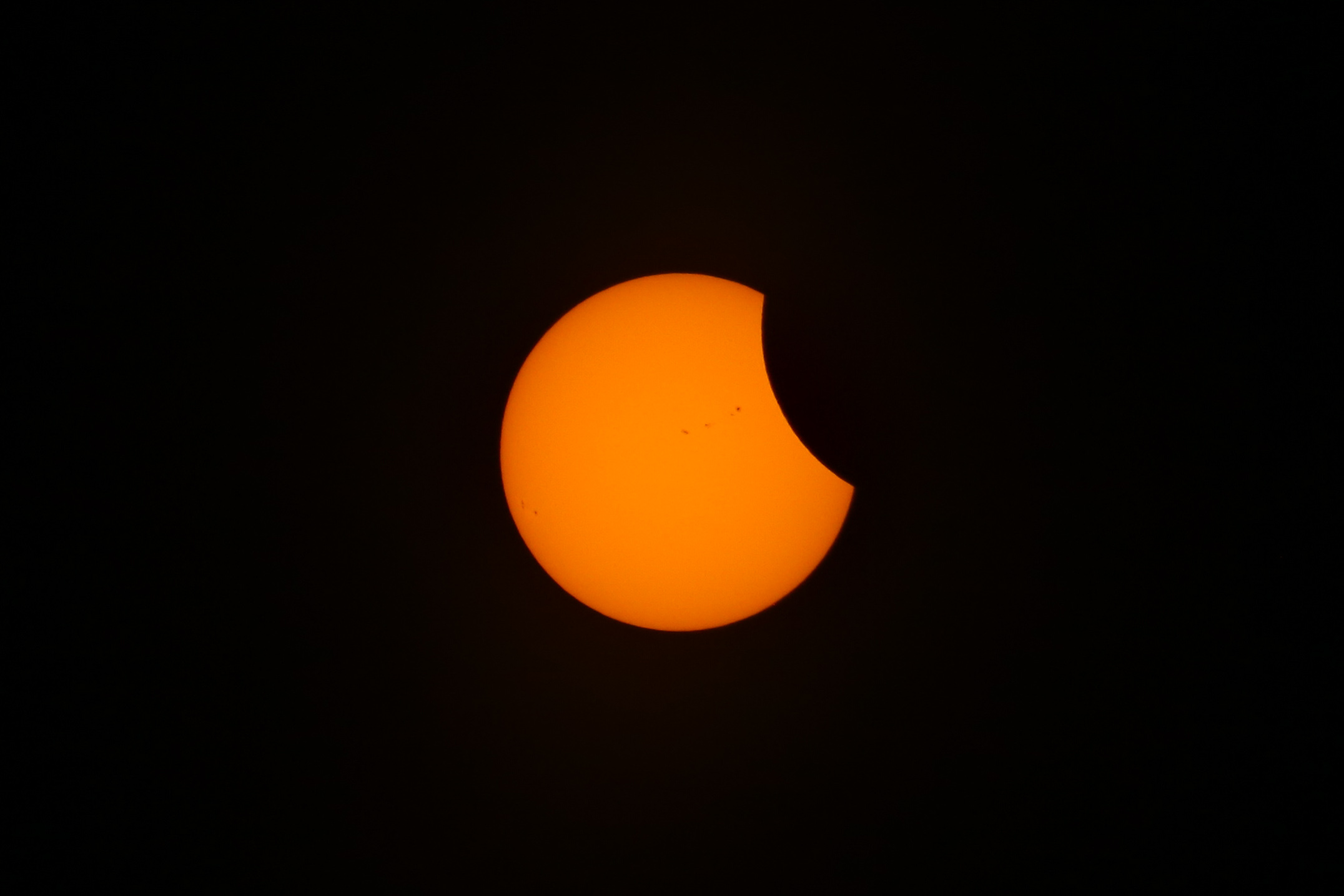 Partial Solar eclipse image in Durham NC 2017. Small portion of the moon is cutting into the sun on the right.