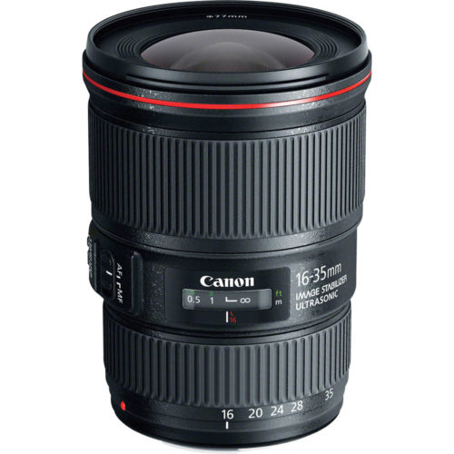 Photo of a black canon lens sitting up with a red ring on the end