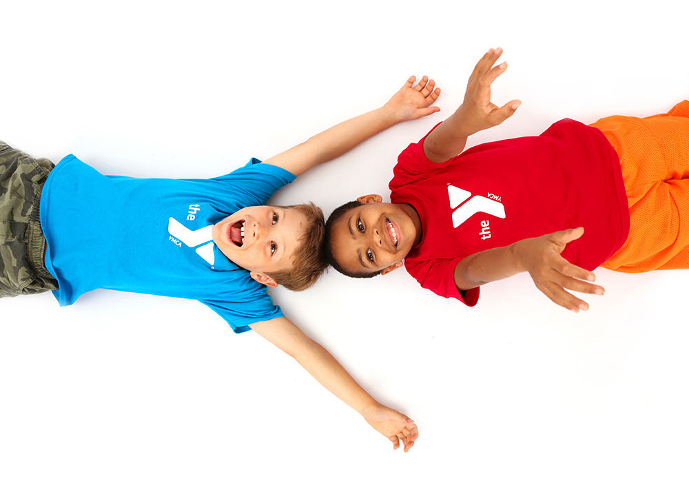Photo of two boys in colorful YMCA shirts laying on a white floor and cheering