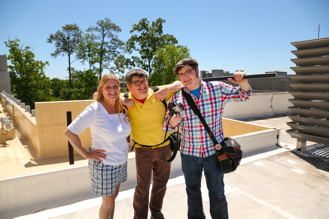 Ken & Colin Huth give a thumbs up with a client on a sunny day on a rooftop