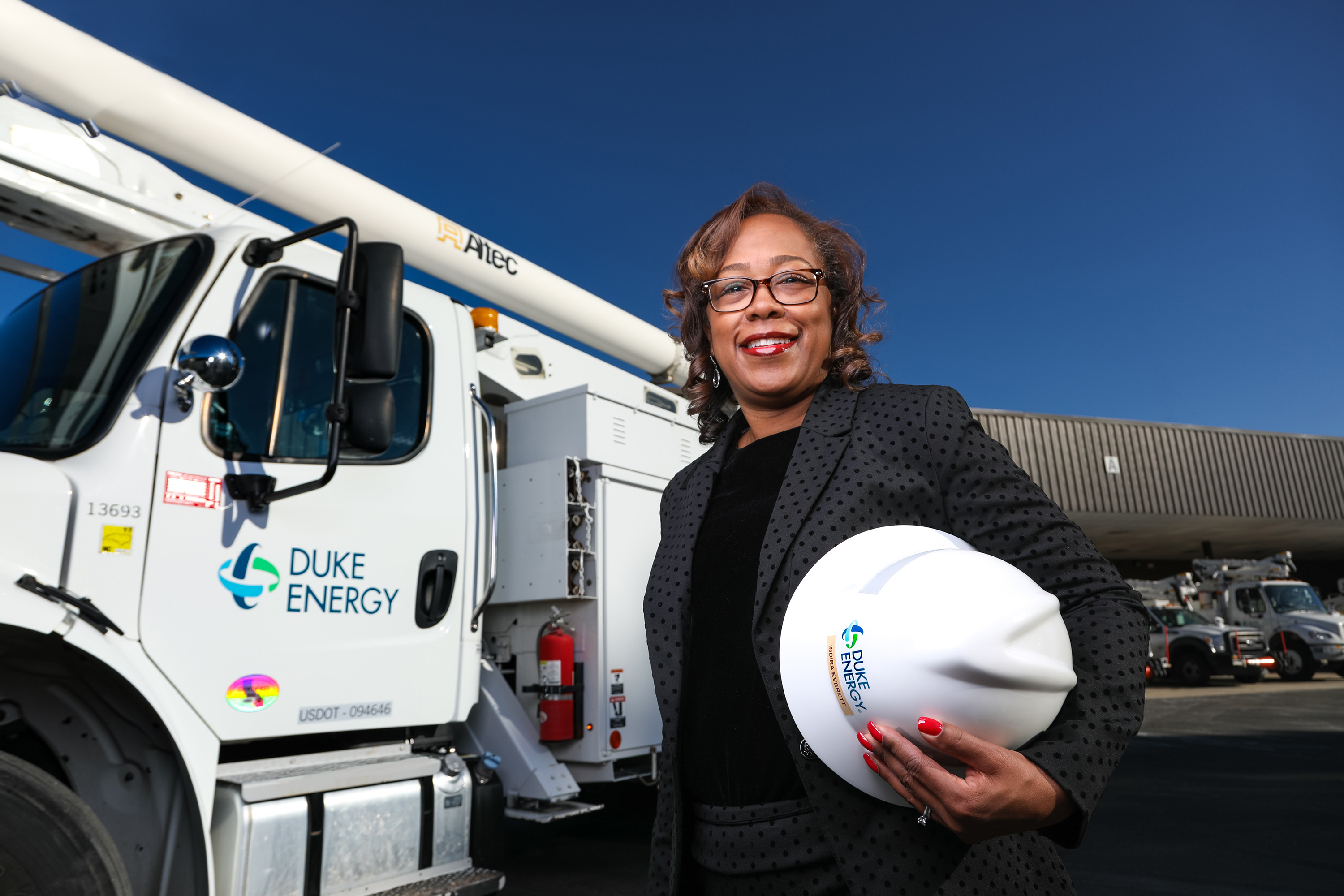 Photo of African-American woman in business suit and a Duke Energy hardhat outside by an electric truck