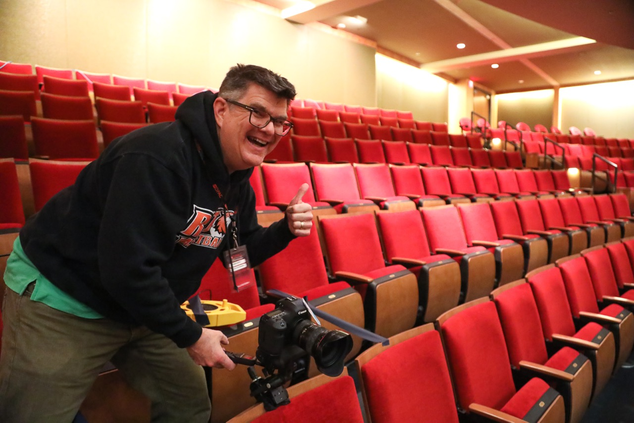 Ken Huth in an RIT sweatshirt in the balcony of a theatre with red seats. A camera is mounted to a chair