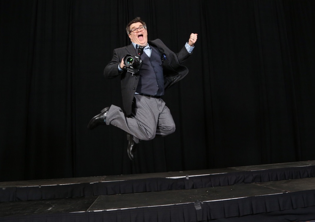 Ken Huth in a suit and with a camera in-hand, leaps into the air for joy and looks a bit silly
